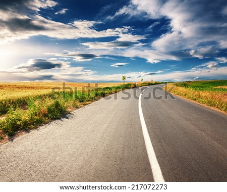 Driving on an empty asphalt road through the agricultural fields on sunny day - stock photo