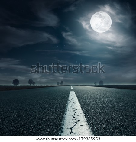 Driving on an empty asphalt road towards the full moon - stock photo