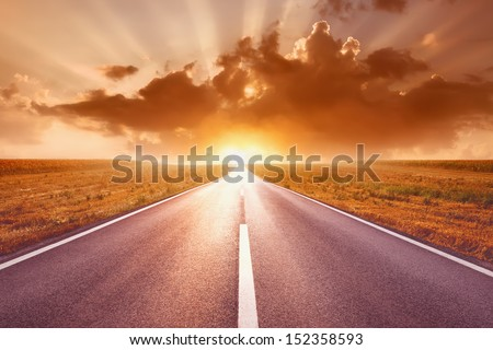Driving on an empty highway to the sun - stock photo