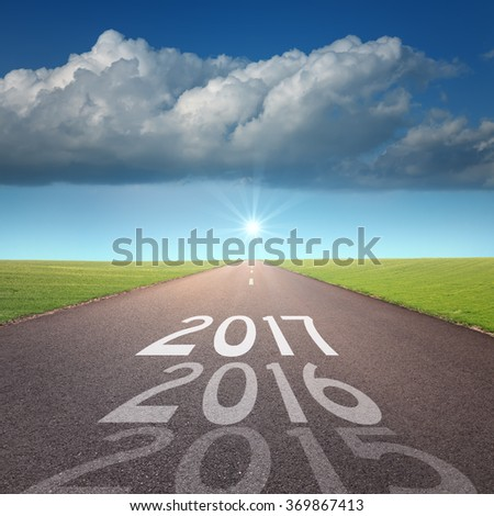 Driving on an empty road towards the big cloud and sun to upcoming 2017 and leaving behind present 2016 and old 2015. Concept for success and passing time. - stock photo