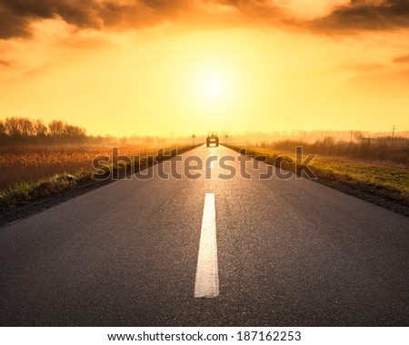 Driving on asphalt road towards the upcoming tractor - stock photo