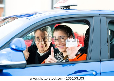 Driving School - Young woman steer a car, maybe she has a driving test, she holding proudly her driving license then she has passed - stock photo