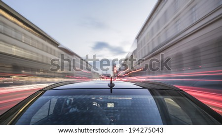 driving through Munich, during day, rigged camera on the rear/trunk of a german black car, bulb exposure - time-lapse, special effects photography - stock photo