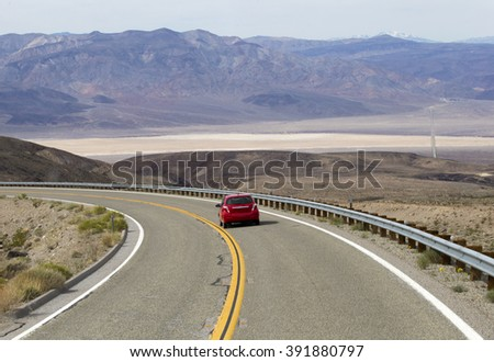 DRIVING TO THE DEATH VALLEY ON HWY 190, March 3, 2016: Small red car is driving to the Death Valley Superbloom - stock photo