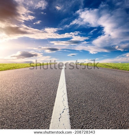 Driving uphill on an empty asphalt road at sunny day - stock photo