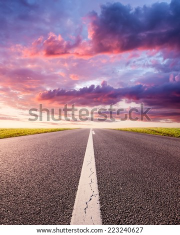 Driving uphill on an empty asphalt road at sunset - stock photo