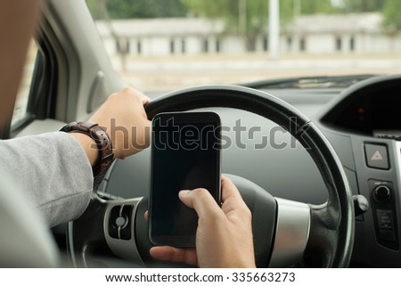 Driving with a mobile phone in hand  - stock photo