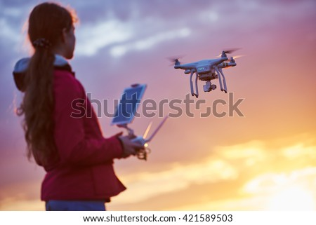 drone flying at sunset - stock photo