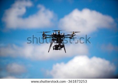 Drone for industrial works flying in sky. - stock photo