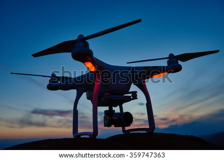 drone quad copter with digital camera at sunset ready to fly for surveillance - stock photo