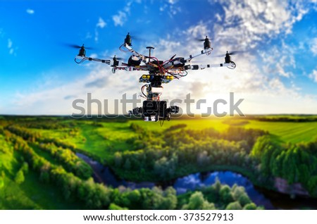 Drone with professional cinema camera flying over a blue calm river in the forests and fields at the sunset. - stock photo