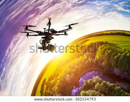 Drone with professional cinema camera flying over a blue calm river in the forests and fields at the sunset. Little planet effect. - stock photo