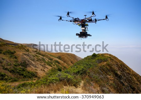 Drone with professional cinema camera flying over Pacific Ocean covered fog and the mountains in California - stock photo