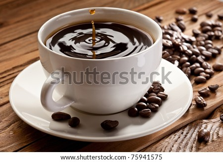 Drop falling into a cup of coffee. On a wooden background - stock photo