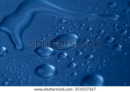 Drop of water on dark blue background  - stock photo