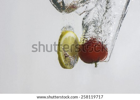 dropped into water lemon and red tomato - stock photo
