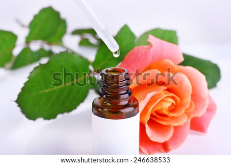 Dropper bottle of perfume with rose on light background - stock photo