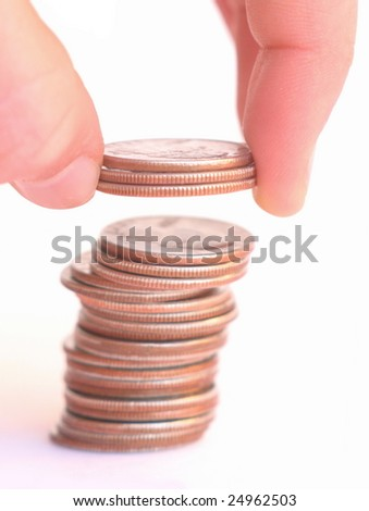Dropping a few quarters onto a stack of coins. - stock photo