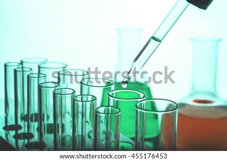 Dropping chemical liquid to test tube, laboratory research and development concept  - stock photo