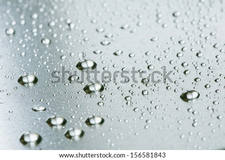 Drops in row on metal surface with shallow depth of field  - stock photo