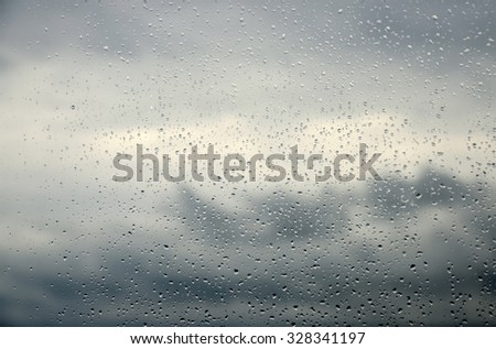 Drops of rain on a window glass.Through the window view of the sea and overcast clouds - stock photo