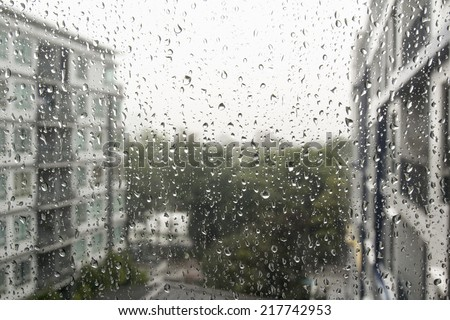 Drops of rain on a window pane, buildings in background. - stock photo