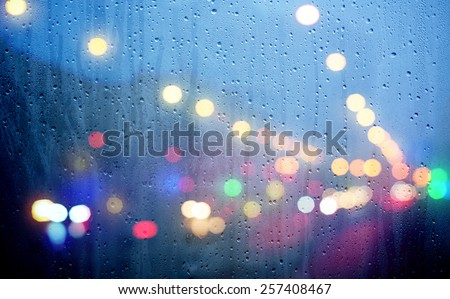 Drops of rain on blue glass with defocused lights. Urban abstract background - stock photo