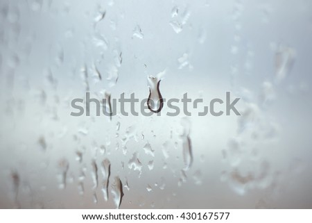 Drops of rain on glass. Rainy day. Rain drop. Use as textured background. Concept of tear. - stock photo