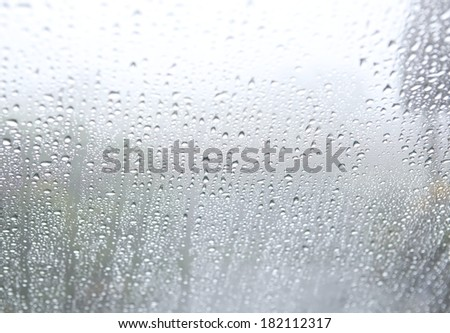 Drops of rain on the inclined window at foggy day.  - stock photo