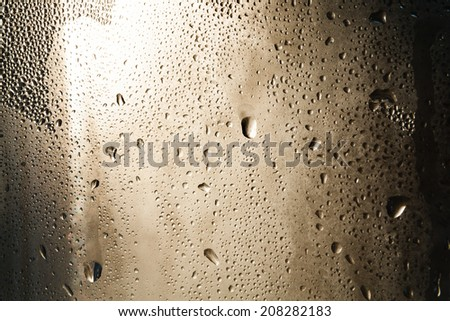 Drops of rain on window with lights background. Atmospheric view. - stock photo