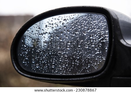 Drops of water on a car mirror. - stock photo