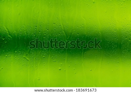 drops of water on glass with green background down in macro lens shot - stock photo