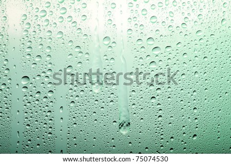 Drops on a glass surface with a green color gradient - stock photo