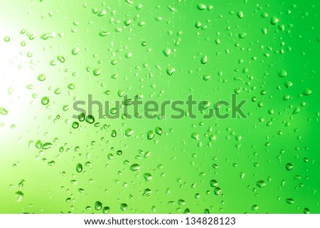 Drops on a glass with a green gradient and sunlight. - stock photo