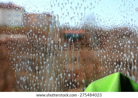 Drops on the windowpane, cleaning window with spray detergent. Glass cleaner on pane. - stock photo