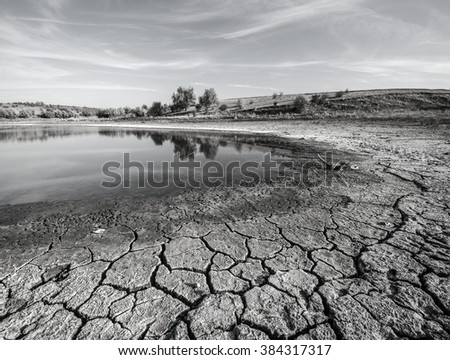 Drought. Chapped ground in foreground. Coast of ephemeral impounded body. Black-and-white photo. - stock photo
