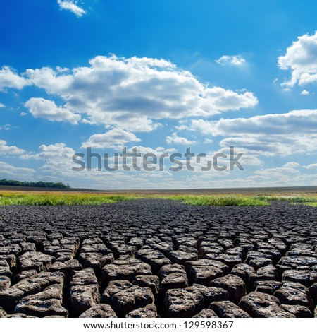 drought earth and blue sky with clouds - stock photo