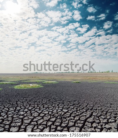 drought earth and hot sun in clouds over it - stock photo