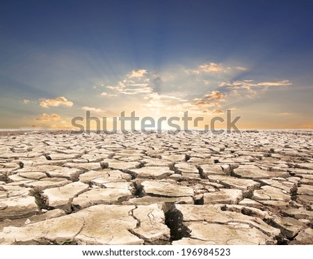 Drought land against a blue sky with clouds sun. - stock photo