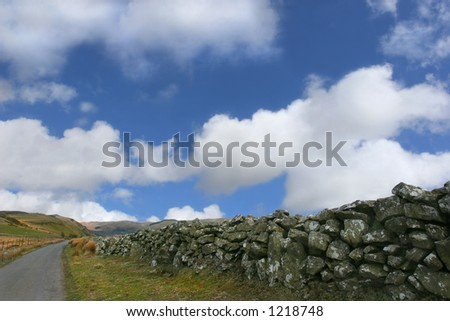 Drovers road in the Cambrian Mountains, Wales, United Kingdom, with a dry stone wall to the right and hills in the distance, set against a blue sky with clouds.. - stock photo