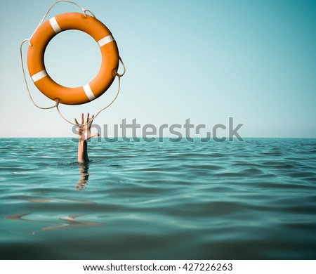 Drown man with rised hand getting lifebuoy help in sea - stock photo