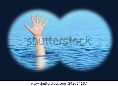 Drowning man needs help. View through binoculars.  - stock photo