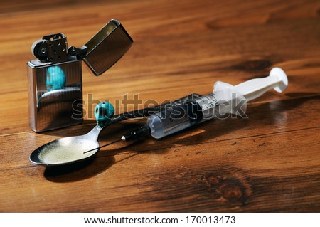 Drug abuse- syringe , spoon,skull  and lighter on the floor - stock photo