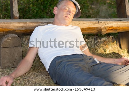 Drug abuser sitting on the ground leaning on a bench feeling sick - stock photo
