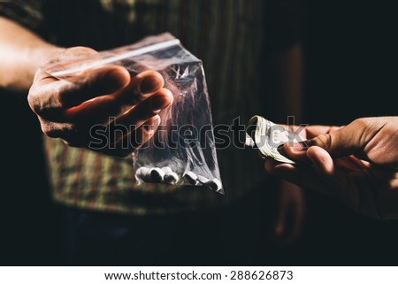 Drug addict buying narcotics and paying - stock photo