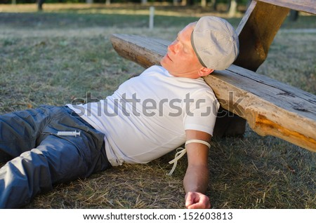 Drug addict collapsed on the ground with his head against a wooden park bench enjoying the euphoria induced by an intravenous drug such as heroin or cocaine - stock photo