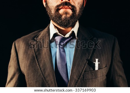 Drug addict in nice suit having a syringe in his pocket - stock photo