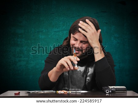 drug addict man with syringe and drags on table - stock photo