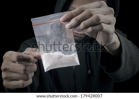 Drug dealer is preparing packet of heroin or cocaine - stock photo