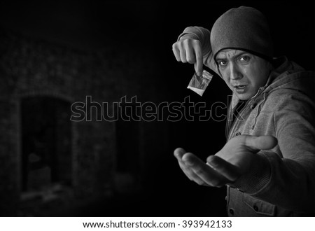 Drug dealer selling heroin or cocaine and demanding money black and white with copy space over old abandoned building. - stock photo